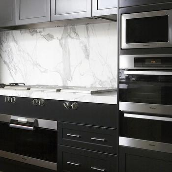 Marco Meneguzzi - kitchens - warming drawer, modern oven, modern kitchen, black and white, black and white kitchen, modern black and white kitchen, black kitchen cabinets, modern black kitchen cabinets, calcutta marble, calcutta marble countertops, calcutta marble backsplash, calcutta marble slab backsplash, microwave nook, convection nook, stacked ovens, stainless steel appliances, modern cooktop, inset cabinets, black inset cabinets, black inset kitchen cabinets, black kitchens, modern black kitchens, black cabinets,