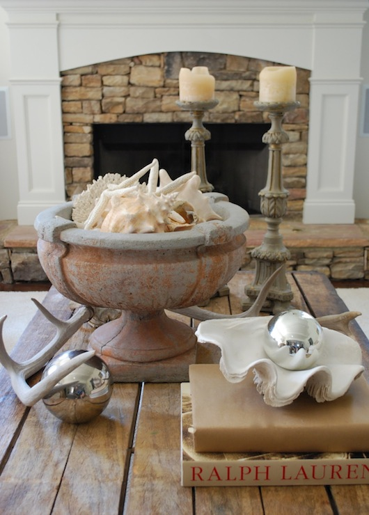 Vreeland Road - living rooms - vignette, seaside living room, clam shell, large clam shell, urn stone urn, decorative antlers, coffee table, rustic coffee table, plank coffee table, wood plank coffee table, stone fireplace, fireplace, decorative antlers,
