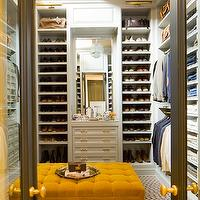 Nate Berkus Design - closets - walk-in closet, glam walk-in closet, tufted ottoman, yellow tufted ottoman, library lights, library sconces, brass library lights, gray closet doors, glass closet doors, shoe shelves, built-in shoe shelves, built-in cabinets, closet built-ins, closet built-in cabinets, mens closet, mens walk-in closet, mustard yellow ottoman,