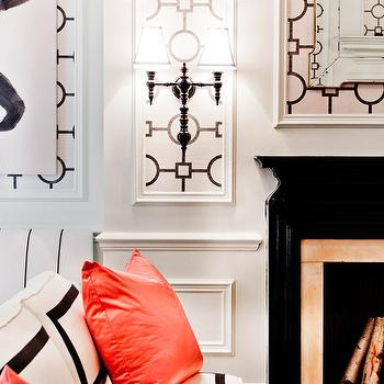 Tobi Fairley - living rooms: black fireplace, glossy black fireplace, fretwork mirror, sconces flanking fireplace, coral pillows, white and black, white and black sofa, geometric wallpaper, wall panels, geometric wall panels, millwork, wainscoting, wainscoted walls, white desk, Hollywood Regency, Hollywood Regency desk, pink lamp shade, vinyl lamp shade, pink vinyl lamp shade, urn lamp, gold trim, white urn lamp, Hollywood Regency lamp, pink chair, French pink chair, faux bois, faux bois fabric, faux bois cushion, trim moldings, wall moldings, black and white living room, hollywood regency living room,