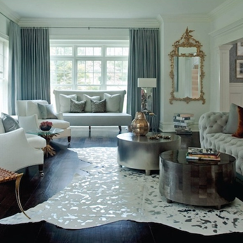 Lynne Scalo Design - living rooms - white cowhide rug, metallic cowhide rug, silver cowhide rug, gray tufted sofa, gray pillows, burnt orange, burnt orange pillows, klismos chair, gold klismos chair, antique mirror cocktail tables, round mirrored tables, mirrored coffee tables, fireplace, blue curtains, blue drapes, ornate mirror, gold ornate mirror, velvet sofa, gray velvet sofa, gray velvet tufted sofa, Oly Studio Adeline Cocktail Table, White and Metallic Cowhide Rug,