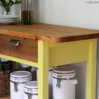The Hunted Interior - kitchens - butcher block island, yellow butcher block island, white canisters, brass hardware, brass pulls, vintage kitchen island,
