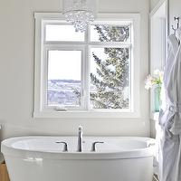 Veranda Interiors - bathrooms - gray bathroom, gray walls, gray paint, tub in front of window, soaking tub, freestanding tub, crystal chandelier, bathroom chandelier, bathroom lighting, sloped ceiling, lighting over tubs, chandelier over tubs, chandelier hanging over tub, chandelier above tub,