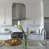 Veranda Interiors - kitchens - galley kitchen, counter-depth refrigerator, shaker cabinets, white shaker cabinets, white kitchen cabinets, marble countertops, mosaic tiles, mosaic tile backsplash, mosaic backsplash, stainless steel appliances, sink in kitchen island, gooseneck faucet, cabinets over refrigerator, cabinets over refrigerator, cabinets above fridge, cabinets above refrigerator,