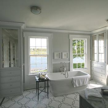 Peter Zimmerman Architects - bathrooms - seaside bathroom, waterfront bathroom, quatrefoil table, black quatrefoil table, master bathroom, waterfront master bathroom, tub in front of window, gray bathroom, freestanding tub, fretwork window moldings, fretwork, mirrored cabinets, mirrored cabinet doors, chair rail, gray walls, gray paint, glass-front bathroom cabinets, single bathroom cabinet, gray bathroom cabinet, marble countertop, wood panels, gray wood panels, mosaic tiles, mosaic tile floor, mosaic floor, bathroom sconces, gray master bathroom, waterfront bathroom, gray master bath, gray bathroom design, Walker Zanger Circolo Pattern, Ralph Lauren Home Marine Porthole Light,