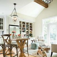 TerraCotta Properties - living rooms - iron candelabra, rustic wood beams, salvaged wood kitchen island, x-base, x-base kitchen island, French cafe counter stools, French cafe barstools, white kitchen cabinets, island lantern, island lighting, open floor plan, floor to ceiling cabinets, built-ins, built-in cabinets, lined built-ins, brown built-ins, counter-depth refrigerator, jute rug, gray jute rug, rolled-arm chair, white rolled-arm chair, Moroccan coffee table, Moroccan table, hundi lantern, hundi lanterns, West Elm Mini Pebble Wool Jute Rug, West Elm Carved Wood Coffee Table, Restoration Hardware Madeleine Armless Counter Stool, Pottery Barn Hundi Lantern,
