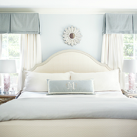 Kara Cox Interiors - bedrooms - blue bedroom, chic bedroom, blue sophisticated bedroom, blue elegant bedroom, blue valance, windows flanking bed, ivory bed, ivory headboard, blue lumbar pillow, blue blanket, white drapes, sunburst mirror, white sunburst mirror, ivory window panels, gold trim, gold mirrored nightstand, rose quartz lamp, pink lamp, mirror nightstands, mirrored nightstands, mirrored bedside tables, white and blue bedroom, Worlds Away Humphreys Antique Mirrored Chest,