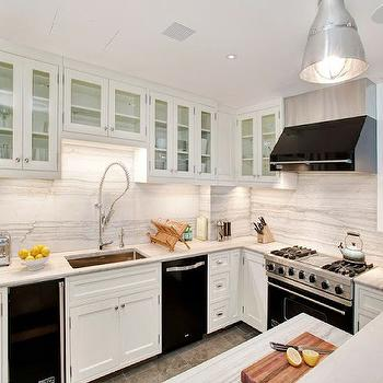 White kitchen with sleek black appliances. Floor to ceiling white