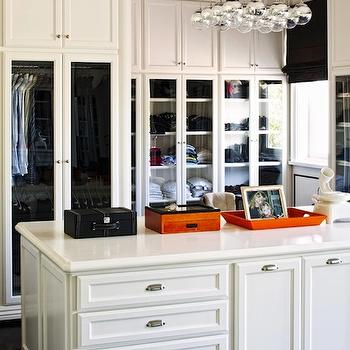 closets - walk-in closet, glam closet, built-ins, built-in cabinets, closet built-ins, closet built-in cabinets, closet island, marble countertops, glass door cabinets, modern pendant, black roman shade, Hermes orange, orange tray, white closet island,