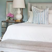 Tobi Fairley - bedrooms - chic bedroom, blue paint, blue walls, gray headboard, gray tufted headboard, gray linen headboard, tufted headboard, linen headboard, gray linen headboard, French bench, gray bench, gray French bench, mirrored chest, mirrored nightstand, white gourd lamp, blue pillow, blue fretwork pillow, gold leaf frame, white hotel bedding, blue stitching, blue rug, antique mirrored nightstand, antiqued mirrored nightstand, Anthropologie Mirrored Dresser,