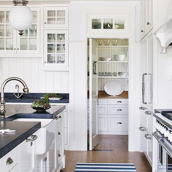 Boston Magazine - kitchens - beachy kitchen, u shaped kitchen, beadboard backsplash, white beadboard backsplash, transom windows, walk-in pantry, farmhouse sink, apron sink, soapstone countertops, wood kitchen hood, wood panel fridge, beehive pedants, island pendants, kitchen lighting, kitchen pendants, white kitchen cabinets, shaker cabinets, white shaker cabinets, kitchen hardwood floors, stripe rug, awning stripe rug, white and blue, white and blue rug, counter-depth fridges, wood counter-depth fridges, coastal kitchen, white coastal kitchen, Kohler Vinnata Faucet, Robert Abbey Beehive Pendant,
