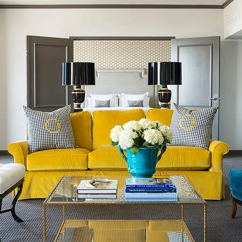 Tobi Fairley - living rooms - gray pillows, velvet pillows, gray velvet pillows, white ottomans, white tufted ottomans, Hollywood Regency ottomans, gray doors, canary yellow, canary yellow sofas, rolled-arm sofa, yellow rolled-arm sofa, peacock blue chairs, peacock blue bergere chairs, bergere chairs, velvet chairs, blue velvet chairs, brass floor lamps, turquoise blue, turquoise blue planter, coffee table, glass-top coffee table, gray moldings, yellow sofa, velvet sofa, yellow velvet sofa, yellow and blue living room, yellow and peacock blue living room, peacock blue and yellow living room, yellow sofas, velvet sofas, yellow velvet sofas,
