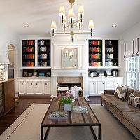 Sally Wheat Interiors - living rooms - arched doorway, art deco cabinet, art deco, art deco credenza, flatscreen TV, fireplace, built-ins, built-ins flanking fireplace, teal lined bookshelves, peacock blue lined bookshelves, silver mirror, silver arch mirror, border rug, flat bar chairs, brickmakers coffee table, gray sofa, modern gray sofa, white roman shades, black ribbon trim, blue paint, blue walls, gold ottomans, modern chairs, black chairs, chevron pillows, gray chevron pillows, tiered chandelier, family room built ins, built ins for family room, books arranged by color, family room, Jonathan Adler Ventana 2 Tier Chandelier, Layla Grayce Eloquence Louis Philippe Silver Mirror,