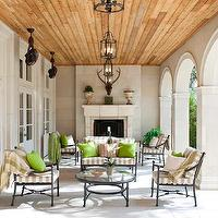 Symmetry Architects - decks/patios - wood plank ceiling, covered patio, wall of French doors, store fireplace, outdoor fireplace, arched doorway, outdoor furniture, wrought-iron furniture, iron lanterns, ceiling fans, covered deck,