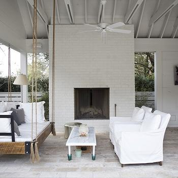 Heather A Wilson, Architect - decks/patios - covered patio, outdoor fireplace, hanging rattan swing, white slipcover chairs, wood kitchen island, stone pavers, silver metallic pouf, outdoor swing, outdoor sofa, outdoor swing sofa,