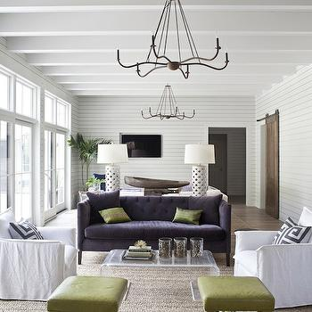 Heather A Wilson, Architect - living rooms: gray fretwork pillows, tongue and groove walls, long living room, narrow living room, built-in TV nook, separate sitting areas, barn doors, sliding barn doors, wall of French doors, iron chandeliers, green x-bench, white slipcover chairs, acrylic coffee table, lucite cocktail table, purple sofa, purple tufted sofa, white lattice lamps, furniture arrangements, separate seating areas, split living room, living room split into 2 areas,