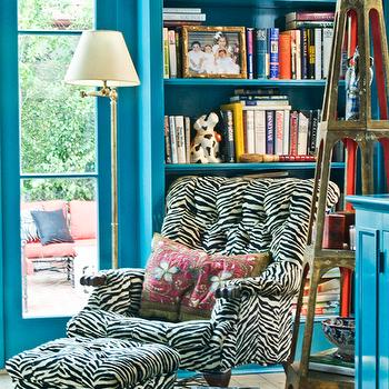 MMR Interiors - dens/libraries/offices - peacock blue office, teal den, tufted chair, zebra chair, zebra tufted chair, zebra ottoman, zebra ottoman, tufted zebra ottoman, wood plank floors, built-ins, teal bookshelf, gold etagere, etagere brass floor lamp, teal walls, teal paint, peacock blue paint, peacock blue walls, turquoise blue cabinets,