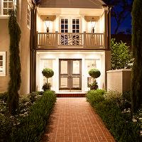 Elizabeth Kimberly Design - home exteriors - carriage house, iron lanterns, boxwood hedges, red brick pathway, bay topiaries, ivy, black front door, juliet balcony, chippendale balustrade, brick pathway,