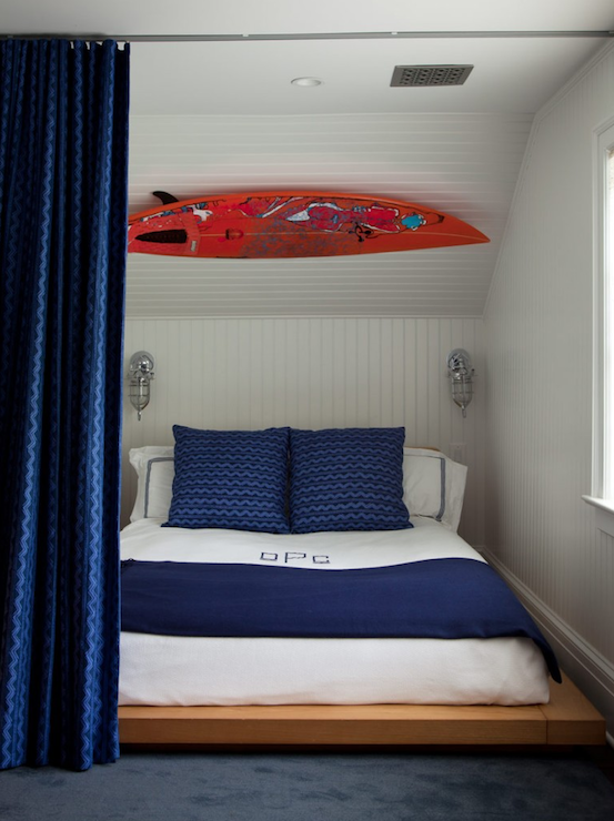 Amanda Nisbet Design - boy's rooms - blue boy's bedroom, surfboard bedroom, beadboard walls, white beadboard walls, platform bed, wood platform bed, blue curtains, blue drapes, marine sconces, bedroom sconces, sloped ceiling, caged sconce, marine sconce, maritime sconce, maritime caged sconce,