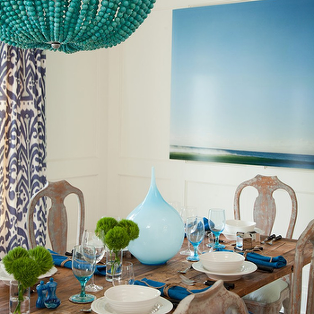Amanda Nisbet Design - dining rooms: abstract art, teal napkins, teal linens, peacock blue napkins, peacock blue linen, seaside dining room, beachy dining room, beaded chandedlier, turquoise blue beaded chandelier, white box beams, wainscoting, white wainscoting, purple ikat drapes, purple ikat curtains, matchstick shades, trestle dining table, gray washed dining chairs, vintage dining chairs, dining chairs, blue vases, blue bottles, turquoise beaded chandelier,
