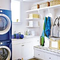 Style at Home - laundry/mud rooms - white and blue laundry room, blue laundry room, stacked washer and dryer, blue front-load washer and dryer, blue stripe rug, blue awning stripe rug, built-in bench, utility sink, shaker cabinets, white shaker cabinets, beadboard, white beadboard backsplash, soffit, white floating shelf, white corbels. woven baskets, storage bench, mudroom, mudroom design, mudroom cabinets, mudroom bench, mudroom hooks, mudroom laundry room, laundry room mudroom, mudroom shelving, mudroom beadboard walls, mudroom beadboard paneling,