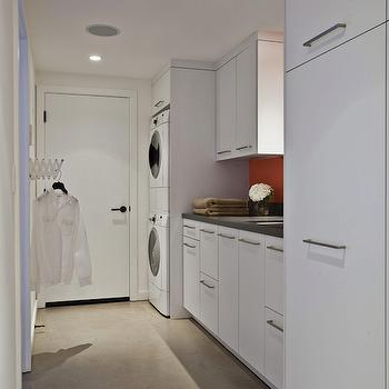Fiorella Design - laundry/mud rooms - long laundry room, narrow laundry room, white laundry room, concrete floors, stacked washer and dryer, red backsplash, black granite countertops, laundry room cabinets, white laundry room cabinets,