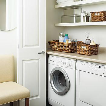 House & Home - laundry/mud rooms - folding doors, laundry room closet, floating shelves, wicker baskets, white front load washer and dryer, hidden laundry room, laundry room doors, laundry room folding doors,