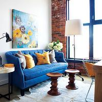 Style at Home - living rooms - azure, blue sofa, cobalt blue, tufted sofa, cowhide rug, white cowhide rug, bone inlay, bone inlay table, exposed brick wall, loft, blue sofa, tufted sofa, blue tufted sofa, crate & barrel sofas, loft living room, exposed brick wall, brick wall, azure sofa, Crate & Barrel Azure Sofa, West Elm Bone Side Table, Eames Walnut Stool, Bertoai Side Chair,