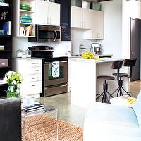 Style at Home - kitchens - seagrass rug, charcoal gray sofa, gray sofa, velvet sofa, gray velvet sofa, acrylic console table, loft, blue chair, blue slipper chair, slipper chair, white kitchen cabinets, frameless cabinets, white frameless cabinets, industrial barstools, chalkboard, stainless steel appliances, loft kitchen, waterfall coffee table, waterfall acrylic coffee table, kitchen chalkboard, chalkboard in kitchen, CB2 Clear Peekaboo Coffee Table,