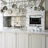 Elle Decor - kitchens - gourmet kitchen, stainless steel appliances, stainless steel pot rack, ivory kitchen cabinets, overlay cabinets, ivory overlay cabinets, white carrara marble, white carrara marble countertop, sink in kitchen island, electric rotisserie, stainless steel backsplash, stainless steel kitchen hood, pot filler, galley kitchen, gourmet galley kitchen,