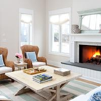 Erica Burns Interiors - living rooms - beachy family room, tan paint, tan walls, tan paint color, white fireplace, wood panel fireplace, wood paneled fireplace, wicker chairs, trestle table, trestle coffee table, white sofas, coffee table, cocktail table, white slipcover sofas, white slipcovered sofas, white sofas, slipcover sofas, blue pillows, ivory rug, celadon rug, green rug, stripe rug, awning striped rug, green mirror, two story living room, wicker chairs, ivory and celadon green, paint color,