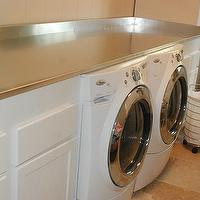 While They Sleep - laundry/mud rooms - white laundry cabinets, laundry cabinets, stainless steel countertop, white washer and dryer, stone tiles, stone floor, rolling hamper, hamper, stainless steel, wood paneled walls, beige, front-load washer and dryer,
