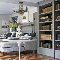 New England Home - dens/libraries/offices - gray doors, built-ins, gray built-ins, gray bookcase, chaise lounge, ticking stripe, stripe chaise lounge, gray pillows, gray fireplace, herringbone, herringbone floor, herringbone hardwood floors, herringbone wood, saarinen table, beaded chandelier, herringbone wood floor, library, den, gray built in cabinets,