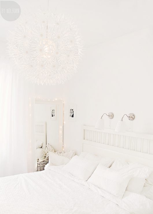 By Holborn - bedrooms - monochromatic bedroom, ethereal bedroom, flower chandelier, white flower chandelier, white headboard, white wood headboard, bedroom sconces, white floor mirror, floor mirrored, bedroom floor mirror, white bedroom floor mirror, sparkly lights, light garland,