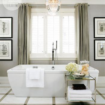 Style at Home - bathrooms - tub in front of window, gray grasscloth, grasscloth wallpaper, gray grasscloth wallpaper, crown molding, millwork, soaking tub, modern soaking tub, etagere, bathroom etagere, mirrored etagere, mirrored bathroom etagere, nickel etagere, nickel bathroom etagere, grommet drapes, gray grommet drapes, bathroom chandeliers, marble tiles, marble bathroom floor, marble bathroom tile floor, bathroom art, floor-mount tub filler, chandelier over tub, chandelier over bathtub,