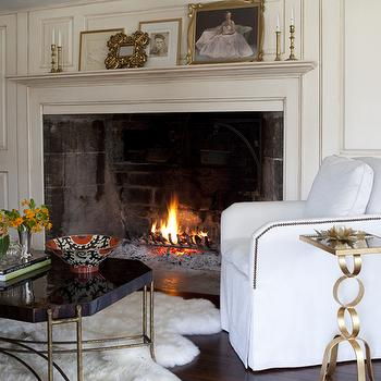 Pimlico Interiors - living rooms - huge fireplace, large fireplace, sheepskin rug, slipcover chair, white slipcover chair, French brass tacks, chair nailhead trim, brass accent table, chain link table, brass chain link table, coffee table, black and gold, black and gold cocktail table, brass coffee table, marble coffee table, black marble coffee table, black cocktail table, brass cocktail table, antique white, wood panel walls, antique white wood panel walls, gold table, gold accent table, gold side table,