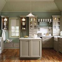 Martha Stewart - kitchens: gray kitchens, cottage kitchens, gray cottage kitchens, u-shaped kitchen, kitchen with central island, painted kitchen islands, taupe colored cabinetry, khaki colored cabinetry, quartz countertops, light countertops, apron sink, farmhouse sink, tray ceiling, vaulted tray ceiling, beadboard ceiling, painted ceiling, teal walls, frosted glass cabinets, open shelving, wood floors, white appliances, mudroom area, kitchen storage, brushed nickel hardware, glass shelves, painted molding, kitchen pendant, vintage pendant, glass pendant, corbel shelves, warm gray kitchens, martha stewart kitchen, martha stewart kitchen cabinets, martha stewart cabinets, seasalt corian, sesalt corian countertops,