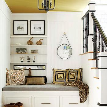 BHG - entrances/foyers - country entryway, coastal entryway, foyer, beadboard walls, white beadboard, painted ceiling, mustard ceiling, wrought iron spindles, geometric pillows, faux fur throw, captains mirror, hanging captains mirror, black and white art, storage bench, built-in storage bench, gray cushion, gray seat cushion, light hardwood floors, wooden stair treads, nautical decor, contemporary lantern pendant, lantern pendant, entryway nook, stairway nook, seating off stairwell, foyer nooks, under the stairs nook,