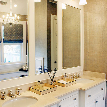 Elsa Soyars - bathrooms - double vanity, his and her sinks, oval sinks, oval undermounted sink, undermounted sinks, brushed nickel faucet, brushed nickel sconces, bathroom sconces, burlap wallpaper, textured wallpaper, recessed panel cabinets, white recessed panel cabinets, drawers, pewter colored hardware, natural stone countertops, brushed nickel faucets, bathroom trays, tray holding perfume, wainscotting, triple mirrors, triple bathroom mirrors, roman blinds, glass chandelier, white double vanity,