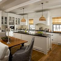 Vallone Design - kitchens - u-shaped kitchen, white Shaker cabinets, Shaker cabinets, black countertops, central kitchen island, farmhouse sink, apron sink, gooseneck faucet, woven pendants, pendants over kitchen island, woven blinds, paneled hood, black window casings, ivory colored subway tile, subway tile backsplash, hardwood floors, wood beam ceiling, recessed lighting, Viking range, Viking oven, oil-rubbed bronze hardware, white slipcovered sofa, table behind sofa, gray slipcovered chairs, brushed metal, buffet lamps, bookshelves, glass fronted upper cabientry, open plan kitchen, family room, open floor plan, open floor plan kitchen, Jamie Young Udaipur Pendant,