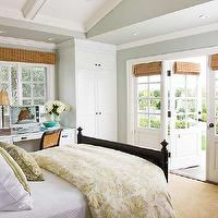 BHG - bedrooms - blue gray cottage bedrooms, blue gray bedrooms, blue gray walls, blue gray paint, blue gray paint color, blue gray paint, vaulted ceilings, bedroom vaulted ceilings, french doors, bedroom french doors, bamboo roman shades, bedroom bamboo shades, bedroom open to yard, bedroom opens to backyard, bedroom wardrobes, white bedroom wardrobes, bedroom cabinets, white bedroom cabinets, bedroom office, bedroom desks, black bound sisal rugs, glossy black beds, black beds, black cottage beds, yellow floral bedding, bedroom recessed lighting,