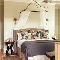 Interior Philosophy - bedrooms - coastal bedroom, coastal colors, sand colored walls, hardwood floors, jute area rug, wing headboard, wing headboard with nailhead trim, bed as focal point, bed wall as focal wall, gray blanket, striped bed skirt, teal coral pillows, coral pillows, beachy pillows, rustic bed canopy, bed canopy, canopy, white sheer canopy, white sheers, brass wall sconces, brass wall sconces flanking bed, ceiling fan, espresso stained nightstands, matching nightstands, bench, bench at foot of bed, sheer bed canopy,