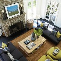 House &amp; Home - living rooms - seagrass rug, open concept living room, tall ceilings, stone fireplace, slate gray sofas, dark gray sofas, pair of sofas facing each other, living room furniture layouts, French doors, ivory walls, ivory white wall color, quince green, quince green pillows, quince green armchairs, wicker basket, basket holding firewood, salvaged wood coffee table, salvaged wood balustrade coffee table, balustrade coffee table, leaning art on fireplace mantel, chunky candleholder, candleholders on fireplace, Hamptons style living room, fireplace screen, ebony stained oak hardwood floors, ebony stained hardwood floors, oak floors, stained oak floors, chartreuse green chairs, chartreuse green, balustrade coffee table, salvaged wood balustrade coffee table,