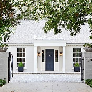 Veranda - home exteriors - gray brick wall, painted brick wall, gravel pathway, white exterior, gray roof, gray tiled roof, dark blue front door, blue front door, blue planters, topiaries, iron gate, lanterns, lanterns flanking front door, celebrity homes, Gwyneth Paltrow home,