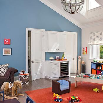Jeneration Interiors - boy's rooms - blue walls, playroom, boys room, kids room, vaulted ceiling, batten and board ceiling, sky light, roman blinds, cabinetry between doors, mini fridge in playroom, orange rug, brown sectional sofa, rocking horse, train table, bin storage, bookcase with bin storage, gumball art, kids play table, storage bin, gray washed wood floors, gray washed hardwood floors, , 3 Sprouts Storage Bin Owl, Restoration Hardware Victorian Hotel Pendant,