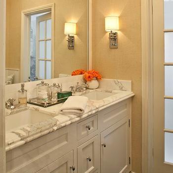 Jeneration Interiors - bathrooms - rafia wallpaper, textured wallpaper, neutral wallpaper, dark hardwood floors, white vanity, double vanity, his and hers sink, vanity nook, mirrored tray, polished nickel faucet, polished nickel hardware, marble countertops, undermount sinks, modern undermount sink, recessed panel cabinet doors, built-in vanity, unframed mirror, built-in mirror, polished nickel wall sconce, frosted glass door, paneled glass door, calcutta marble, calcutta marble countertops,