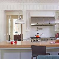 Jeneration Interiors - kitchens - all white kitchen, white beadboard, beadboard walls, beadboard ceiling, range wall, white subway tile, subway tile, white subway tiled backsplash, barrel kitchen hood, stainless steel range, stainless steel gas oven, potfiller, white cabinetry, white kitchen cabinetry, white cabinets, wood countertops, solid wood island countertops, black barstools, farmhouse sink, apron sink, kitchen island, central kitchen island, industrial holophane pendants, polished nickel and glass kitchen pendants, built-in microwave, warming drawer, stainless steel microwave, stainless steel warming drawer,