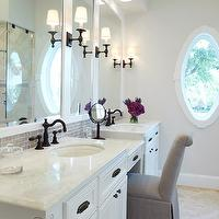Marie Flanigan Interiors - bathrooms - Benjamin Moore - Sheep's Wool - spa bathroom, spa like bathroom, soft gray walls, pale gray walls, oval window, travertine tiled floors, travertine floors, white marble countertops, oval undermount sinks, his and hers sinks, master bathroom, oil rubbed bronze faucets, oil rubbed bronze sconces, white recessed panel vanity, gray crackled glass mosaic backsplash, gray mosaic backsplash, gray linen vanity chair, gray vanity chair, recessed lighting, pot lights, soothing wall color, male up vanity,