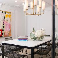 Marie Flanigan Interiors - dining rooms - white walls, abstract art, brightly colored abstract art, metal based parsons dining table, parsons style dining table, wire chairs, modern wire chairs, antique brass chandelier, demi john, stacked books, flowers, contemporary dining room, modern dining room, hardwood floors, jute rug, ebony stained hardwood floors,
