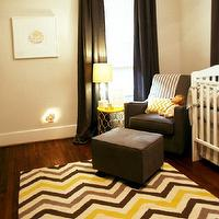 Marie Flanigan Interiors - nurseries - modern nursery, gray and yellow nursery, modern boys nursery, modern baby boys nursery, brown and yellow nursery, pale gray walls, light gray walls, hardwood floors, charcoal gray drapes, zigzag area rug, yellow and brown zigzag rug, yellow metal accent table, yellow accent table, dark gray glider, dark gray ottoman, white crib, faux bois table lamp, white tree trunk lamp, faux bois lamp, striped gray throw, yellow chevron pillow, stuffed lion, scooped arm glider, modern gray glider, yellow and gray nursery, chevron rug, yellow and gray chevron rug, yellow and brown rug, yellow and brown chevron rug, boy nursery, boys nursery, boys nursery design,